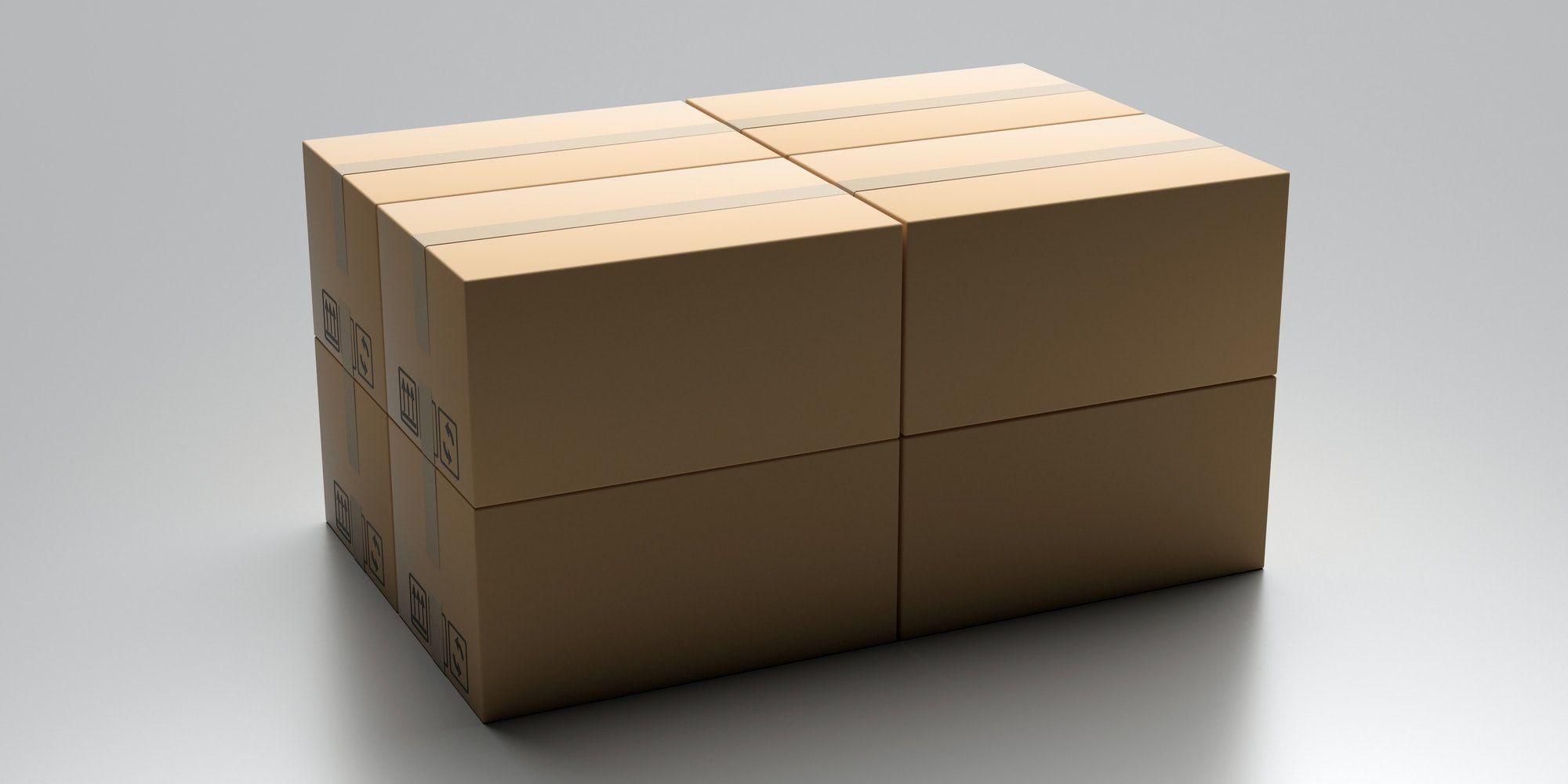 Cardboard packages stack on gray industrial floor.